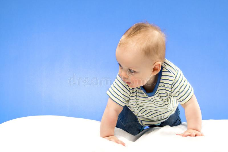 Bright portrait of adorable baby boy on the blue background stock photo