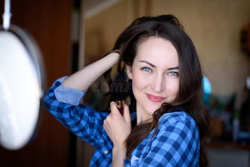 Bright portrait of a smiling woman with natural make-up round make-up mirror with brush in hand in the bedroom interior stock photography