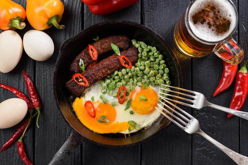 Bright protein meal of fried organic eggs, sausages and peas served for two with beer and bright chili and belle peppers on black. Background above view royalty free stock photography