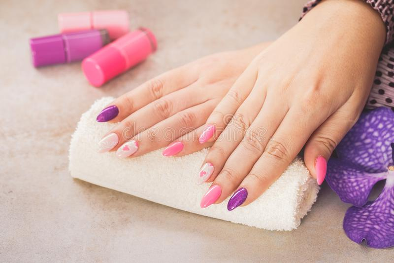 Bright purple and pink manicure. On female hands. Macro, selective focus, blank space stock images