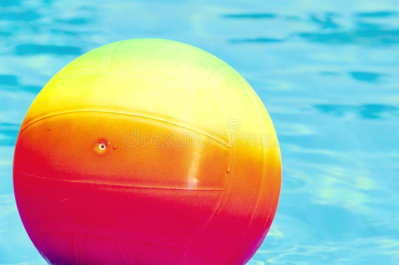 Bright rainbow ball in a swimming pool turquoise water. Concept of a joyful summer vacation. Idea of outdoor games in. The summertime royalty free stock images