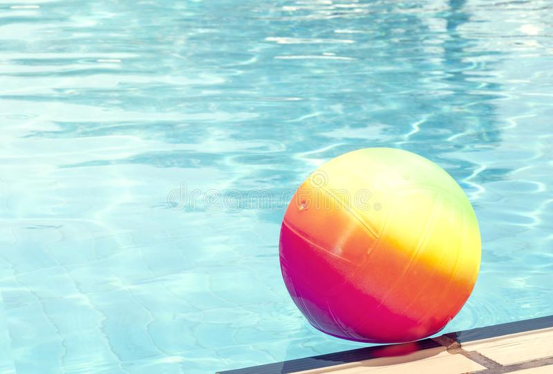 Bright rainbow ball in a swimming pool turquoise water. Concept of a joyful summer vacation. Idea of outdoor games in. The summertime. Copy space for text stock image