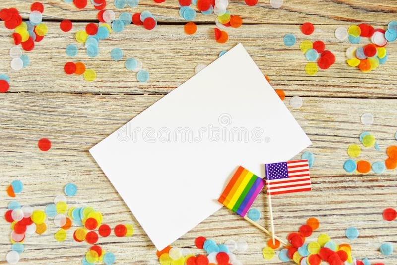 Bright rainbow gay flag on wooden background, paper confetti top view with space for text, mocup, copy space. LGBT community. stock photos
