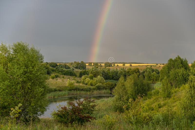 Bright rainbow over the pond, ravine and tree planting.  stock image