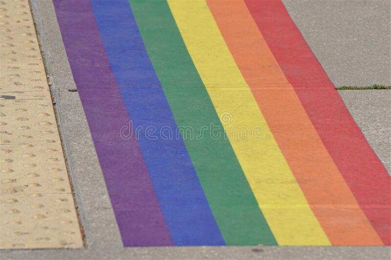 Bright rainbow on sidewalk at crosswalk royalty free stock photo