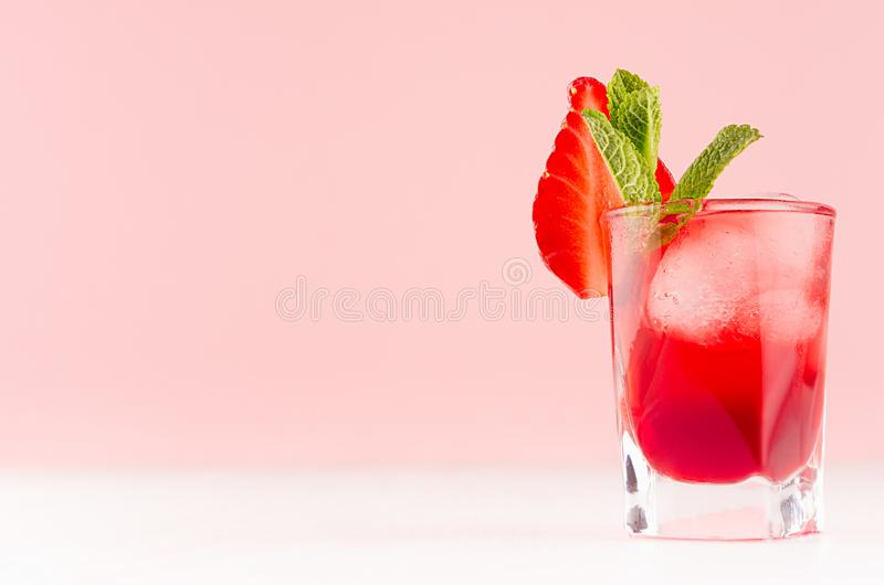Bright red alcoholic drink in shot glass with strawberry slice, ice cubes, green mint in trendy modern bar interior in pastel pink. Color royalty free stock images
