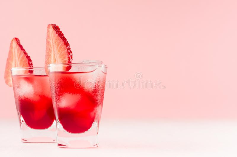 Bright red alcoholic shots in two shot glasses with strawberry slice, ice cubes in trendy modern bar interior in pastel pink color. On white wood board royalty free stock images