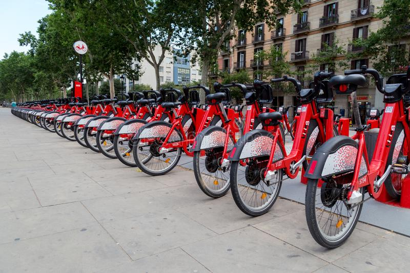 Bright red bicycles available for rent parked in a row at Passeig de Lluis Companys. Barcelona, Spain - July 9, 2019: Bright red bicycles available for rent stock photo