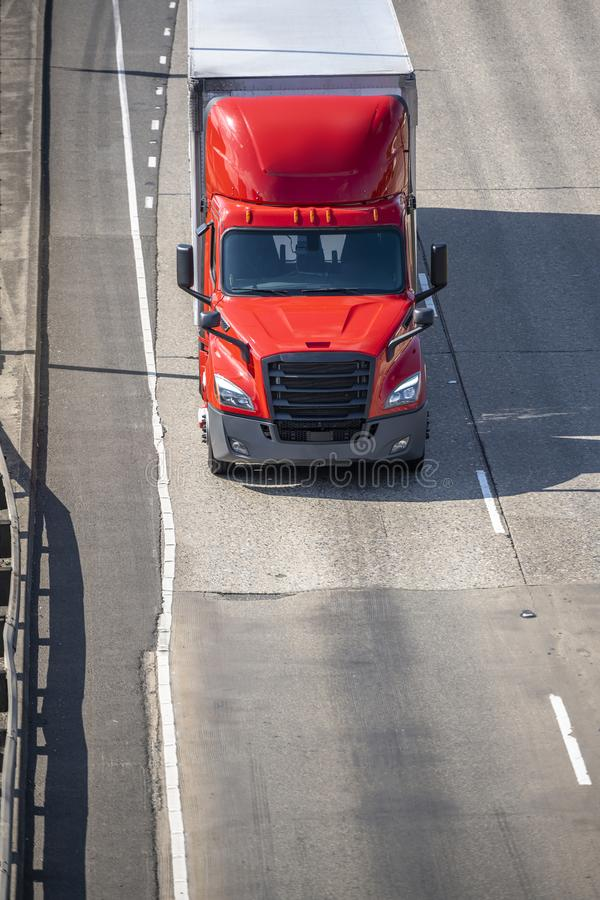 Bright red big rig semi truck transporting commercial cargo in dry van semi trailer driving on the road. Big rig red long haul bonnet professional heavy-duty royalty free stock image
