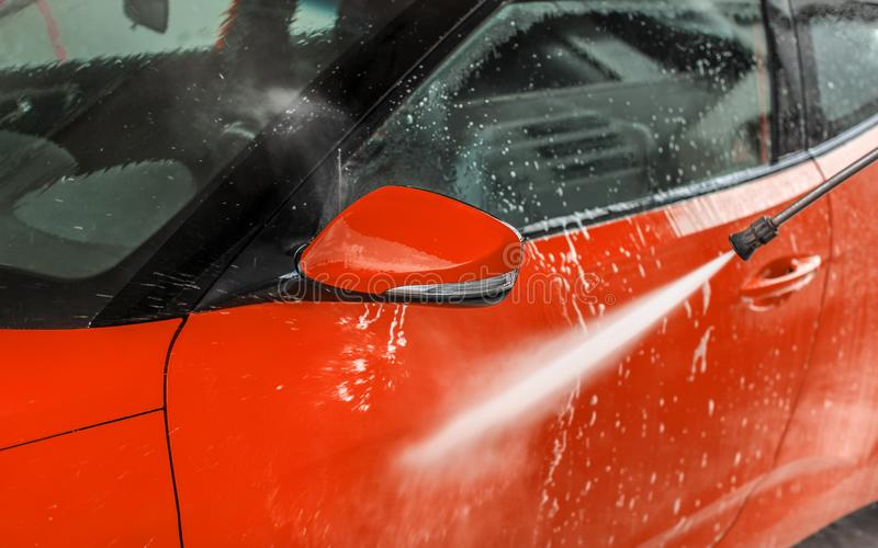 Bright red car washed in self serve carwash, detail on high pressure water jet stream spraying on front door side royalty free stock photo