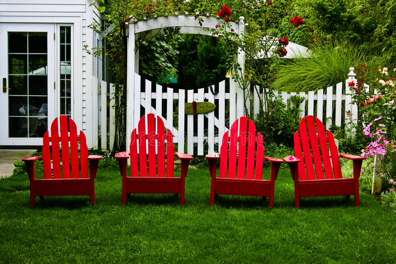 Bright red chairs in a beautiful garden. Red Adirondak chairs lounging in the garden stock photos