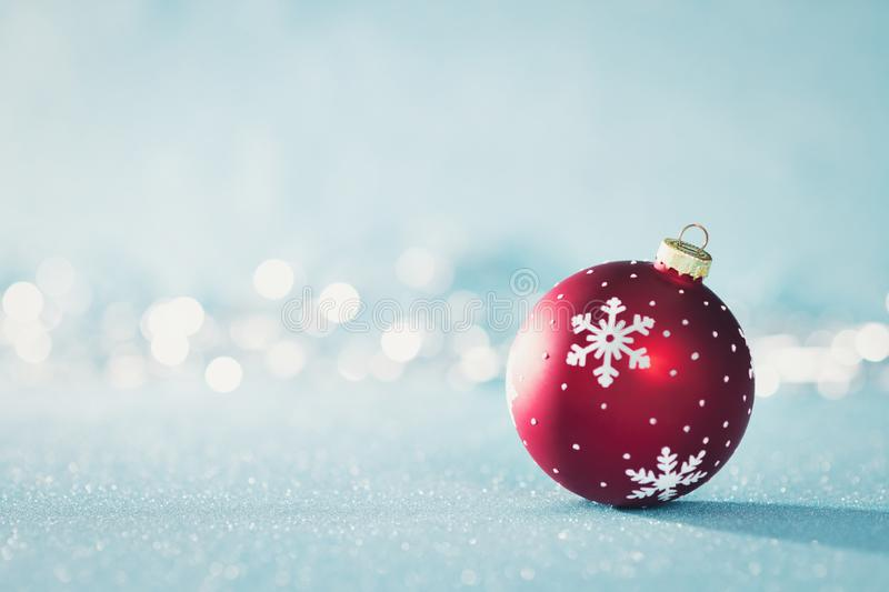 Bright Red Christmas Bauble in Winter Wonderland. Blue Christmas background with defocused christmas lights. royalty free stock images