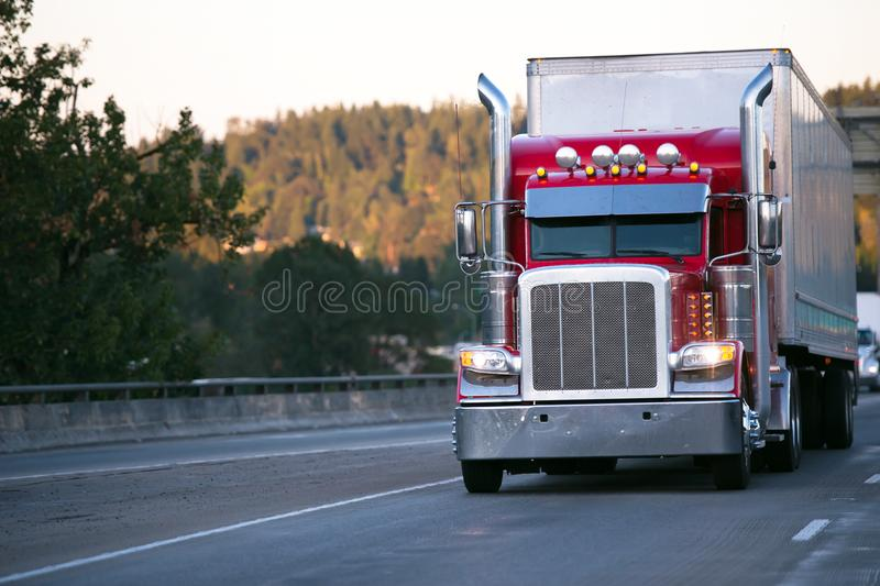 Bright red classic big rig semi truck with trailer move on evening road with turn on headlight. Bright red classic big rig semi truck with high exhaust pipes and stock images