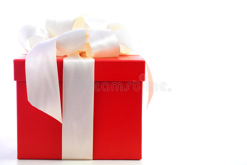 Bright red festive gift box. Bright red festive holiday gift box beautifully wrapped in cream white satin ribbon, on white wood table royalty free stock photography
