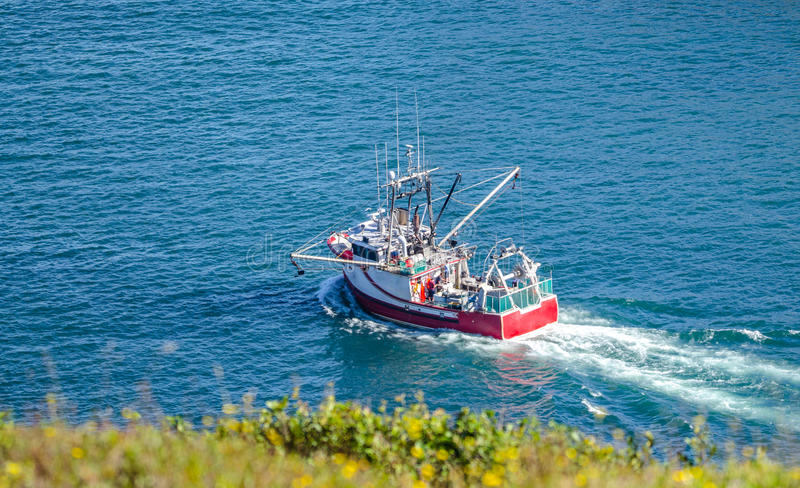 Bright red fishing boat heads out to sea from St. John's harbor Newfoundland, Canada. Bright red fishing boat heads out to sea on sunny summer day from St. John stock images