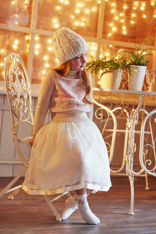 Bright red-haired little girl in a white hat and a beautiful dress is sitting in an autumn cafe. Redhead girl with big blue eyes. And a beautiful sweater meets royalty free stock photos