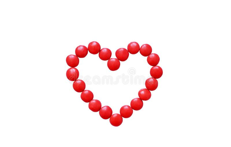 Bright red heart. Heart on a white background. Milk chocolate candy on Valentine`s day. Bright red heart. The contour of the red dots. Heart on a white royalty free stock photography