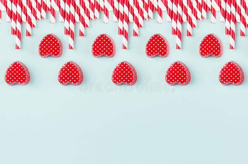 Bright red hearts and cocktail straws as decorative border on mint pastel paper background. Valentine`s day youth design concept art stock image