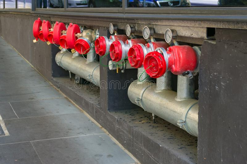 Bright red hydrant booster valves with metal pipes and red caps. Bright hydrant boosters in a row with metal pipes and red caps. Industrial urban infrastructure royalty free stock photos