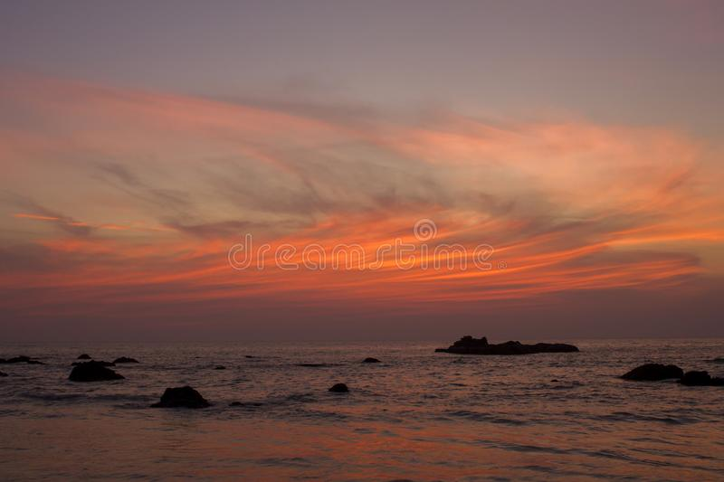 A bright red lines of clouds in the dark blue sky of sunset against the evening sea and rocks stock image