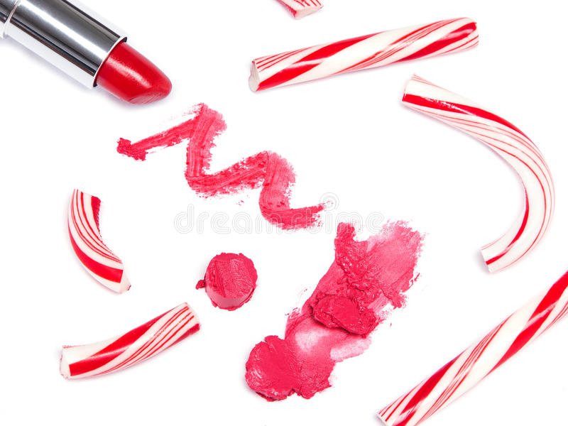Bright red lipstick with crushed Christmas candy. Trendy lip makeup. Bright red lipstick with crushed Christmas candy on white background royalty free stock image