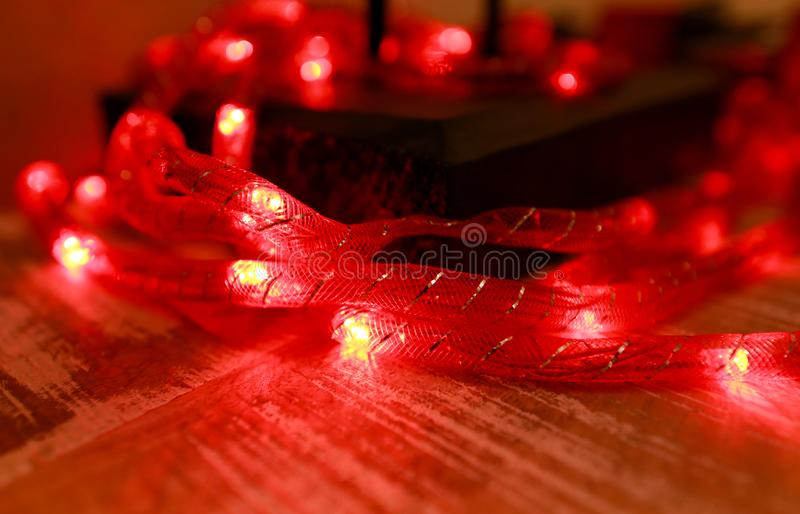 Bright red New Years and Christmas rice lights. Abstract red light background. Decorative flashing lights, ornaments to christmas. stock photo