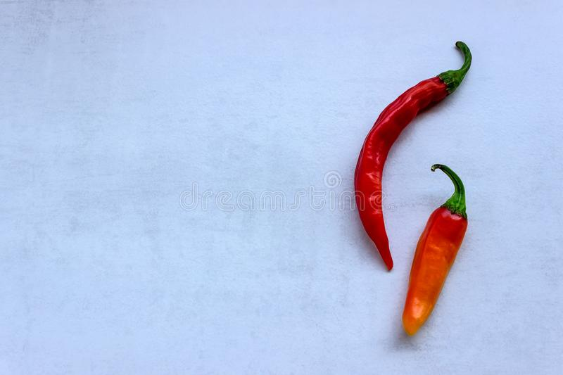 Bright red and orange chili peppers on light stone background. stock image