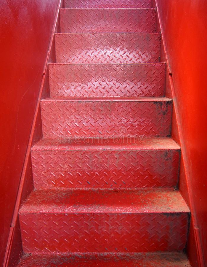 Bright red painted metal staircase with steps made of steel plate with a textured surface and smooth plate walls stock photos