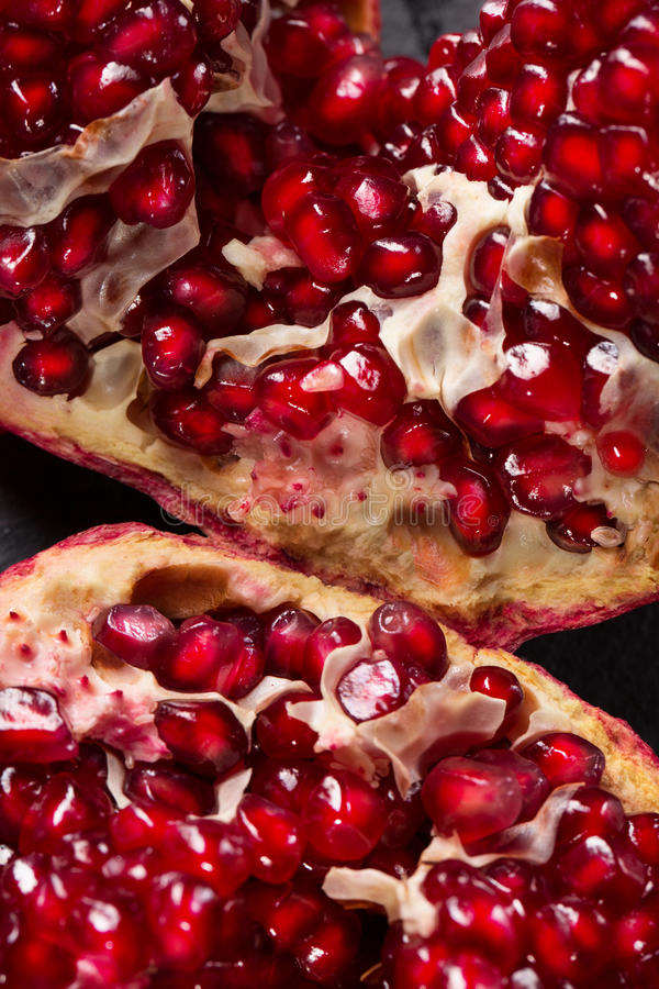 Bright red pomegranate broke down into parts on a black background. Natural, fresh garnet for desserts and beverages. royalty free stock photography