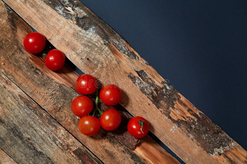 Bright red ripe tomatoes on branch covered with water drops composed on wood planks stock photo