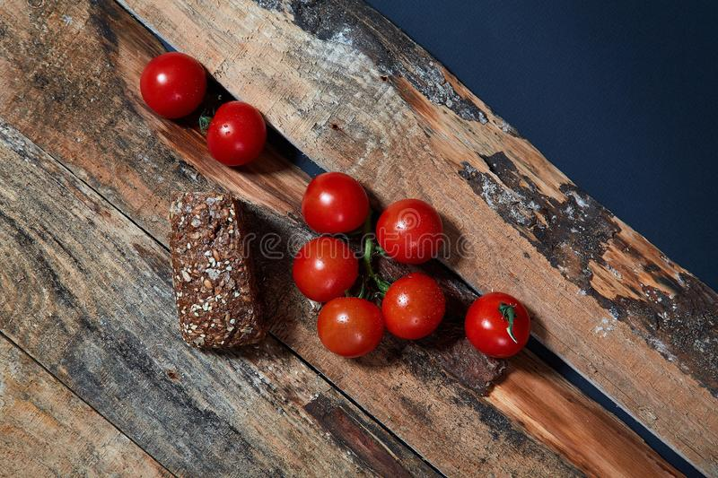 Bright red ripe tomatoes on branch covered with water drops composed on wood planks stock image