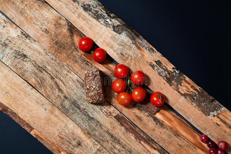 Bright red ripe tomatoes on branch covered with water drops composed on wood planks stock photos
