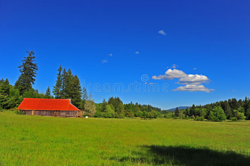 Bright red roof on an old barn in a meadow royalty free stock photography