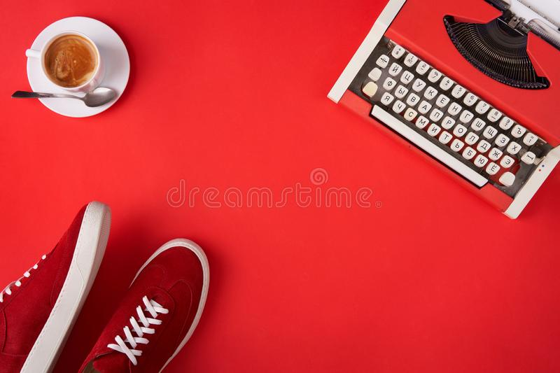 Bright red shoes, typewriter and coffee cup on red background stock photo