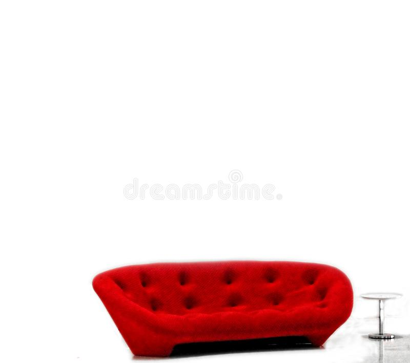 A bright red sofa or couch its against a white background of white royalty free stock photography