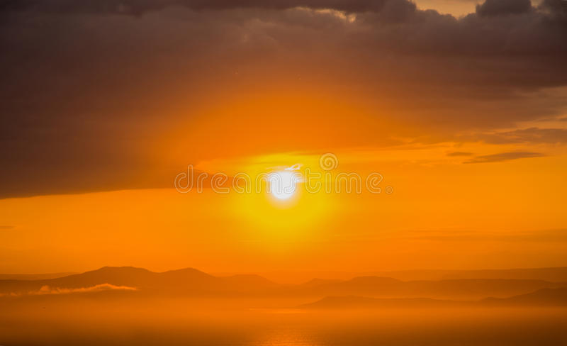 A bright red sunset over the sea, after the storm. Scarlet sunset over water and lots of clouds. stock image