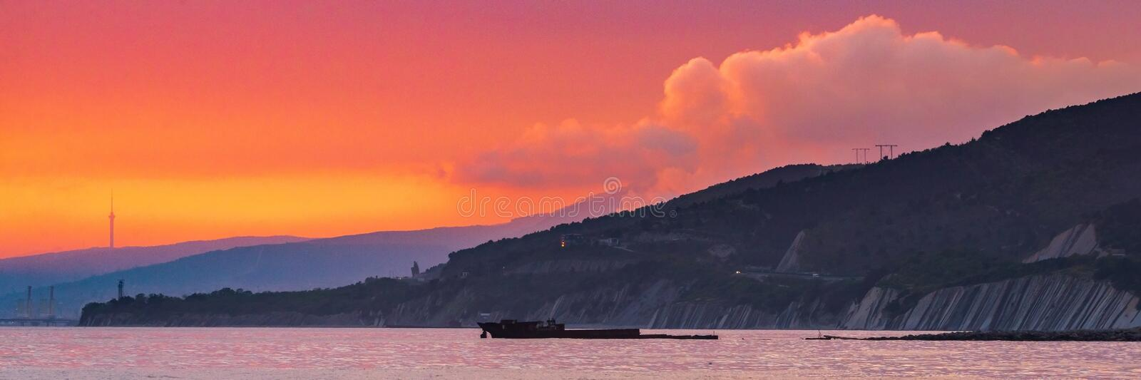 Bright red sunset sky over city and mountains stock images