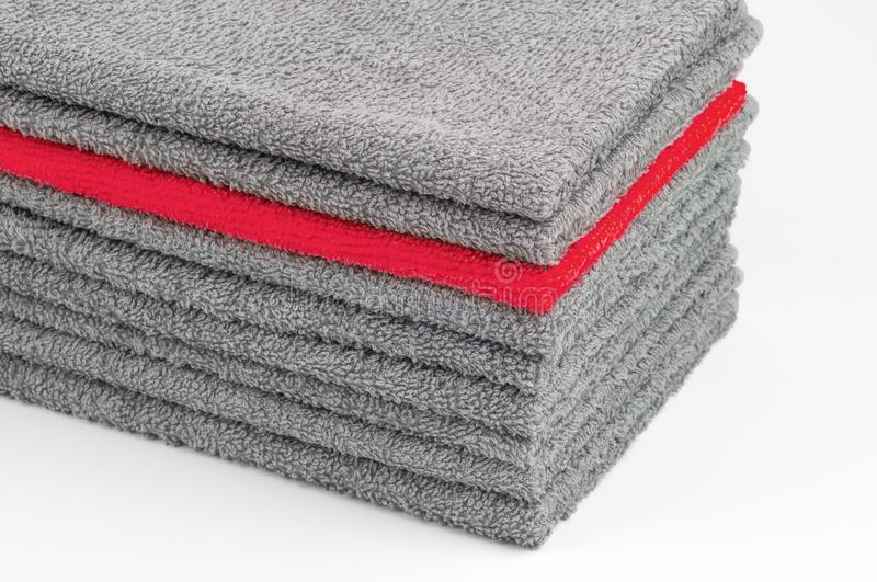 Bright red terry towel in stack of other gray ones. white background. color conceptual contrast. Bright red terry towel in a stack of other gray ones. white stock image