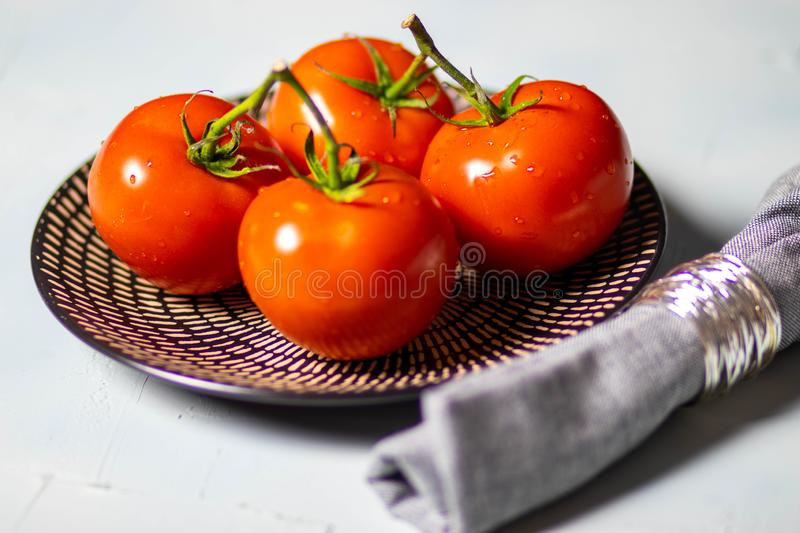 Bright red tomatoes on a plate royalty free stock image