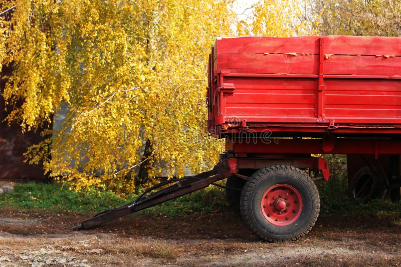 Bright red tractor trailer on a background of yellow leaves. Rural, rustic autumn landscape. Bright red tractor trailer on background of yellow leaves. Rural stock photography