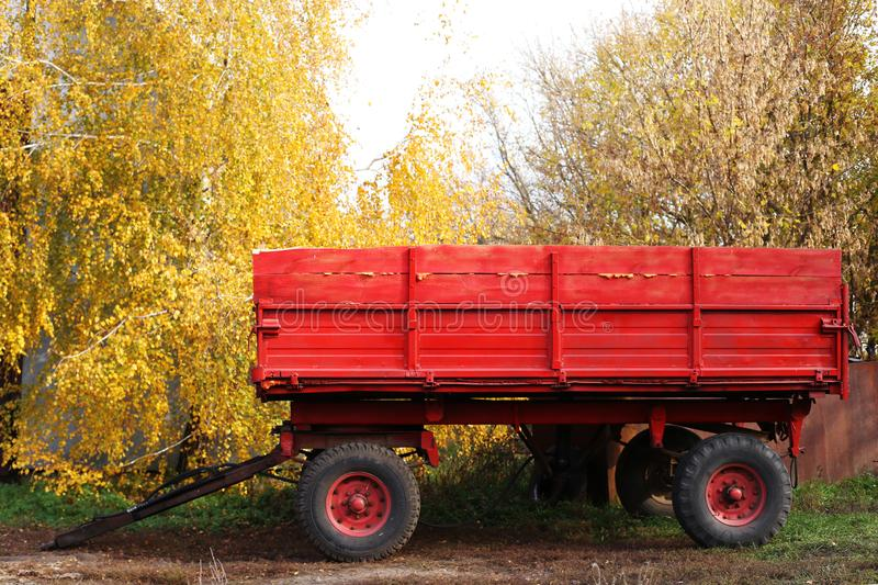 Bright red tractor trailer on a background of yellow leaves. Rural, rustic autumn landscape. Bright red tractor trailer on background of yellow leaves. Rural royalty free stock photography