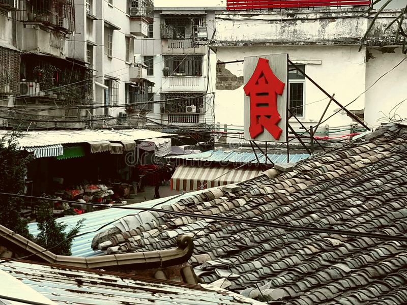 A bright red word for ` food` in slums. A bright red word for ` food` in the slums is followed by a bustling vegetable market royalty free stock image
