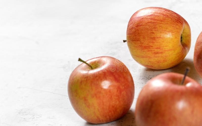 Bright red and yellow apples - fuji kiku variety - on white board, sapce for text left royalty free stock photo