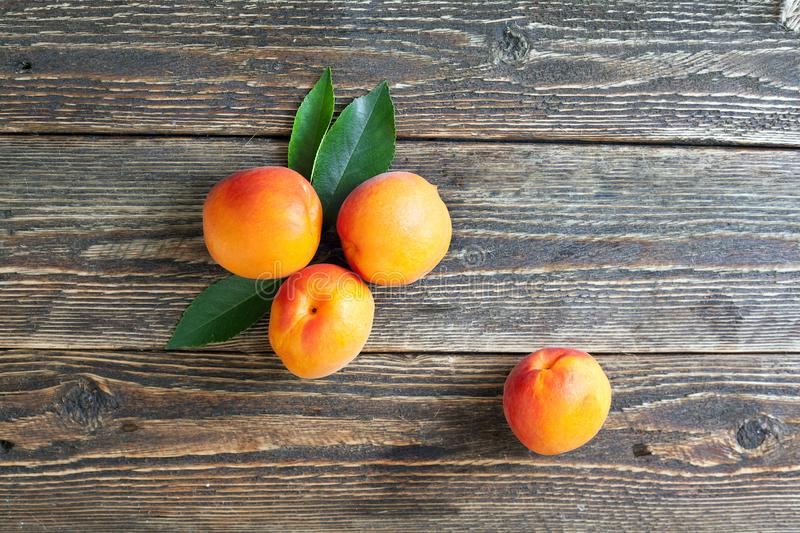 Bright ripe apricots lie on a wooden table stock photo