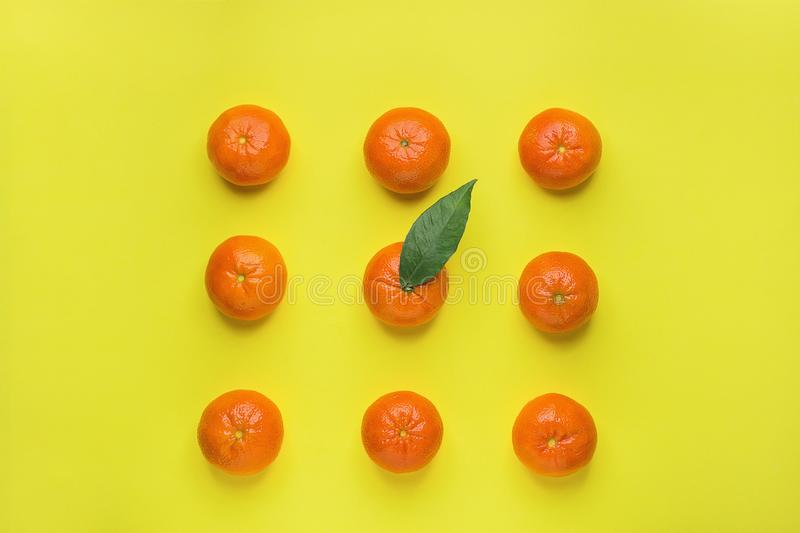 Bright Ripe Tangerines Arranged in Rows in Square One with Green Leaf in Middle. Yellow Background. Food Knolling. Styled Creative. Image. Tropical Fruit stock images