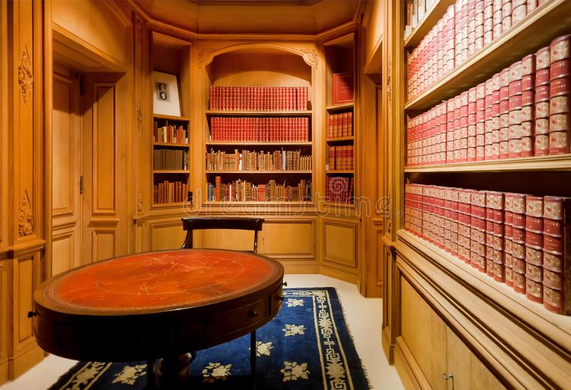 Bright room with ancient books on bookshelves, paper volumes, antique wooden furniture of the Royal Library stock image
