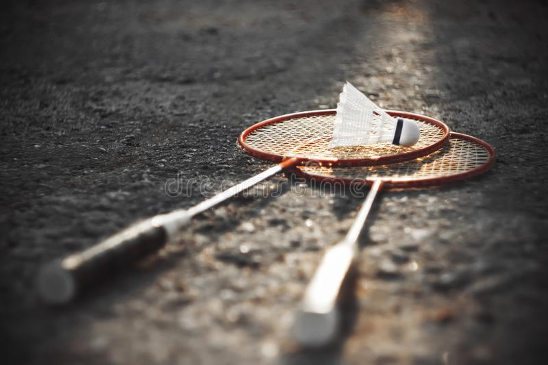 Bright scarlet badminton rackets and white shuttlecock. Black and white image, in which a bright scarlet color highlighted badminton rackets and white stock image
