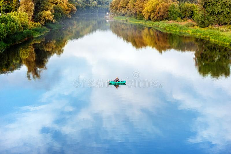 Bright scenic landscape of river in bright multicolored autumn forest with colorful trees. Blue sky reflection mirrored royalty free stock photos