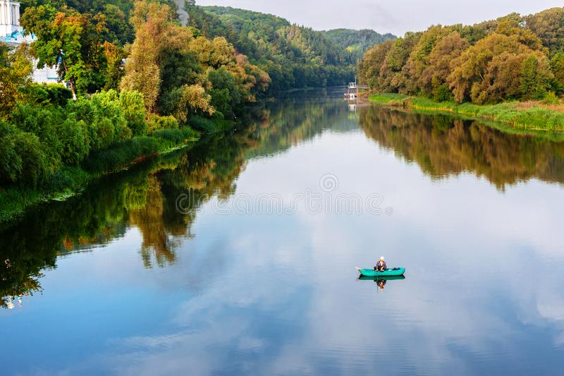 Bright scenic landscape of river in bright multicolored autumn forest with colorful trees. Blue sky reflection mirrored. In pond surface.Fisherman fishing in stock images