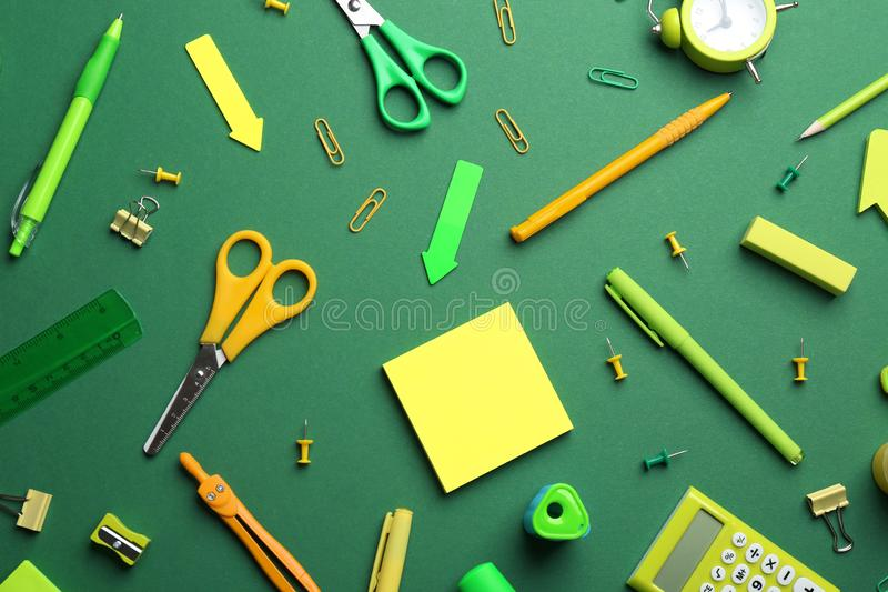 Bright school stationery on green background. Flat lay royalty free stock image